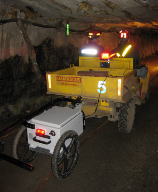 The MineComms Mapper™ is being towed by a mine jeep. The hand-tow bar is in its rest. The passenger is holding the tablet computer.